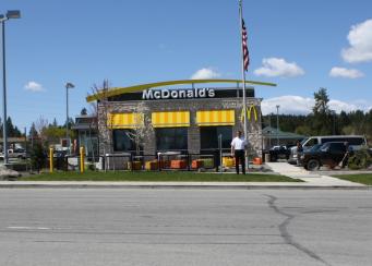 Tim Skubitz, in white, at his McDonalds in Newport, Wash., looks across the highway into Oldtown, Idaho. Photo: Jessica Robinson [KPLU]